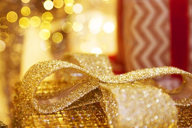 Золотые сверкающие подарочные коробки с бантом с боке из огней. рождественское понятие. макро.