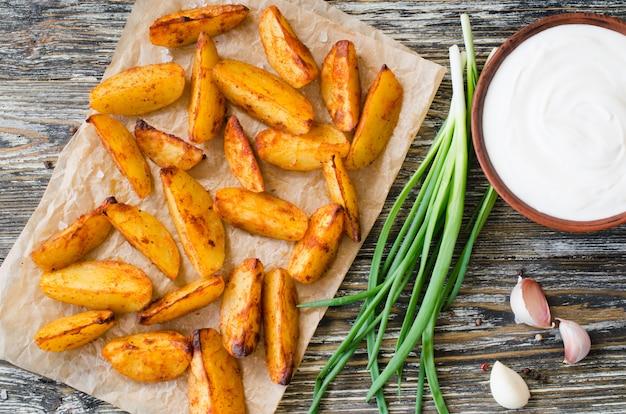 Золотые пряные картофельные дольки обжаренные или запеченные в духовке с чесноком, соусом и луком.