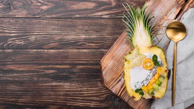 Golden spoon and fruit saladin half of pineapple