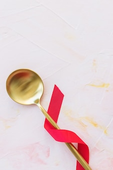 Золотая ложка в красной ленте на розовом