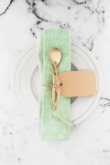 Golden spoon and napkin tied with string on white plate against textured backdrop