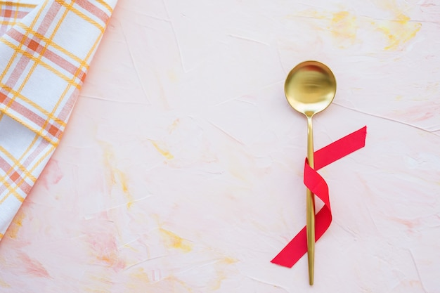 Golden spoon in red ribbon and kitchen towel on a pink background