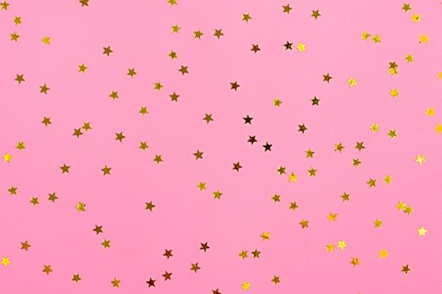 Golden star sprinkles on pink. festive holiday background. celebration concept. top view,
