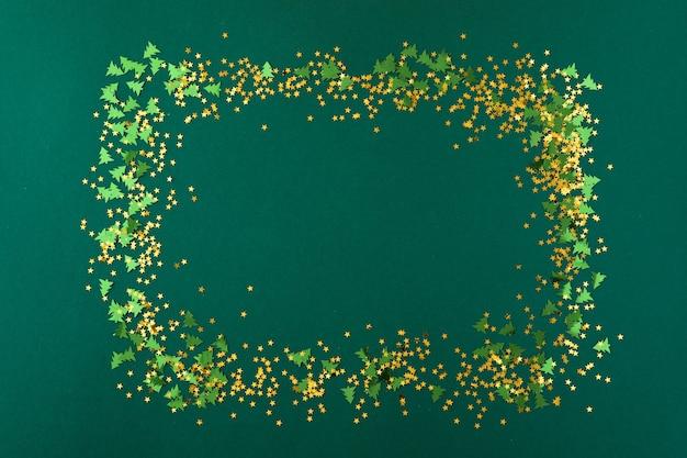 金色の星と緑のクリスマスツリーは、緑の背景に紙吹雪フレームを形作った。上面図、フラットレイ
