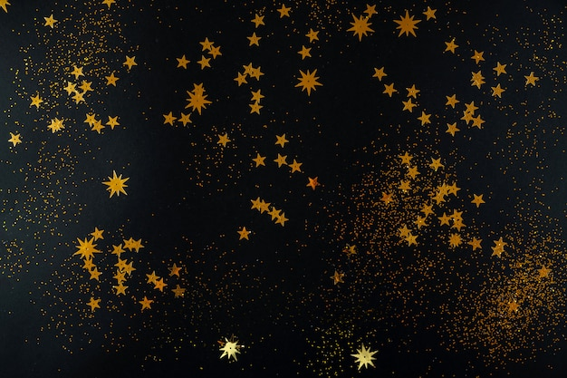 Golden stars on black background. flat lay, top view.