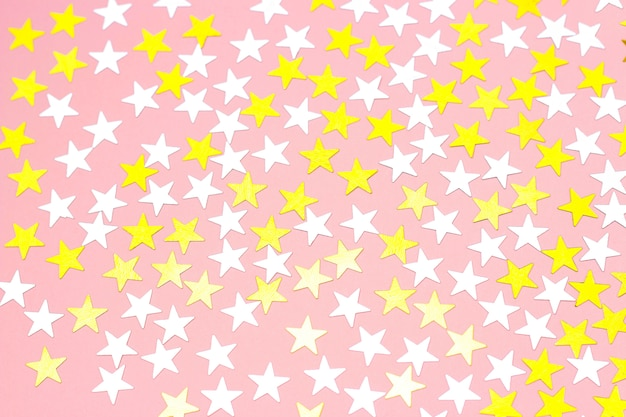 Golden stars of confetti on a white background, top view