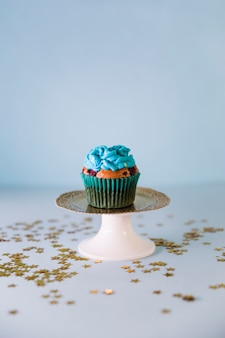 Golden stars spread over the fresh tasty birthday cupcake on cakestand on blue backdrop