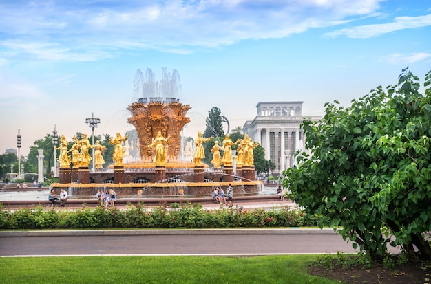 Golden statues of the fountain friendship of peoples at vdnh in moscow among summer greenery. caption: robostation