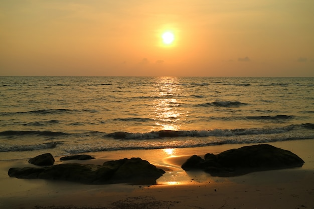 Golden sun setting over the wavy sea of thailand