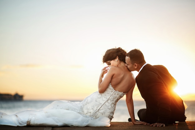 Golden sun shines behind groom kissing bride's shoulder while they rest on the shore