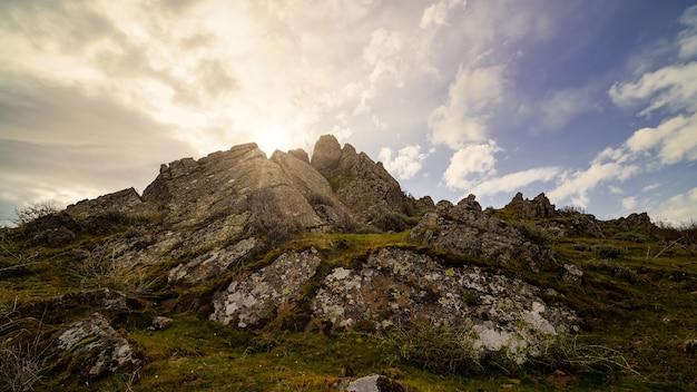 바위와 목가적 인 분위기 뒤에서 나오는 태양 광선으로 산에서 황금빛 일출