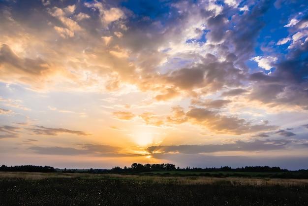 Золотой восход или закат в облачном небе с солнечными лучами летом над лугом