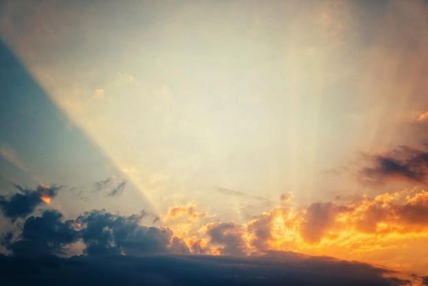 푸른 하늘에 대한 황금빛 일몰, 밝은 태양 광선이 구름을 통과합니다
