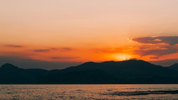 산 바다 해안에 황금 일몰