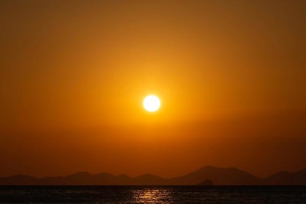 背景の海の山の線に沈む黄金の夕日写真のコピースペースの80%