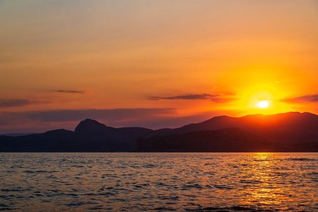 바다 해안의 산 위로 황금빛 일몰
