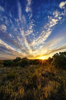 カラフルな空に太陽光線と白い雲と黄金の夕日。