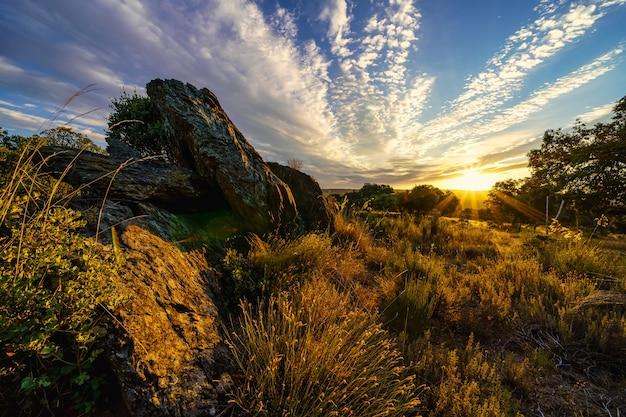 大きな岩を照らす太陽光線のある黄金の夕日