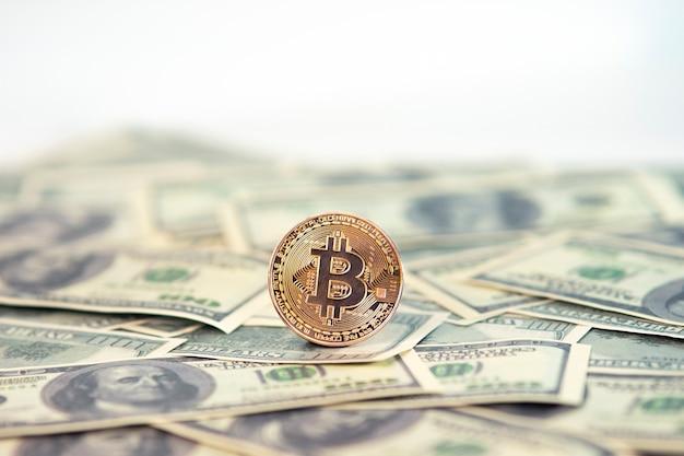 Золотая символическая монета биткойн на банкнотах долларов. обменять биткойн наличные на доллары