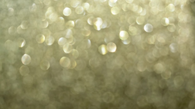 The golden texture of glitter paper reflected light bokeh background