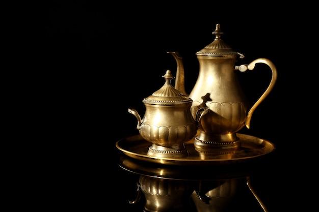 검은 배경에 주전자와 설탕 그릇과 황금 트레이