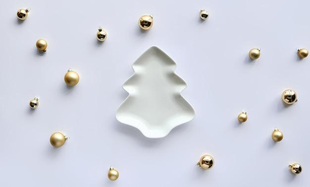 黄金の装身具、白い紙の上にクリスマスツリーの形をしたプレートの周りのクリスマスつまらないもの。冬の休日のためのトレンディな最小限の季節限定フラットデザイン。