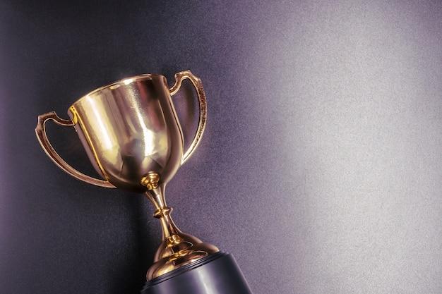 Золотой трофей на черном фоне