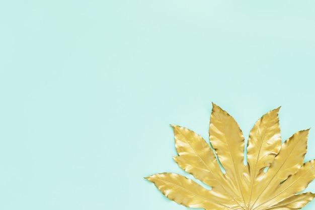 Золотой тропический лист на бирюзовом фоне мятного цвета. минимальная осенняя экзотическая концепция с копией пространства. копирование пространства, вид сверху.