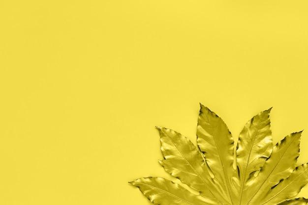 Золотой тропический лист на желтом фоне. минимальная осенняя концепция с копией пространства. копировать пространство вверху