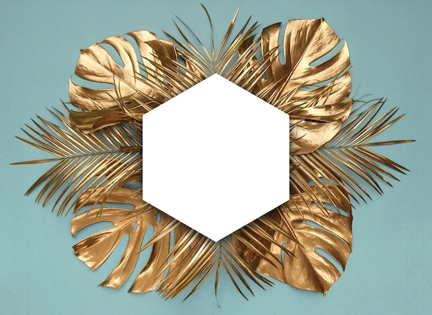 Golden tropical leaves on desaturated blue background