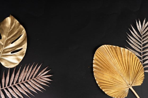 Золотые тропические листья на черном фоне с копией пространства