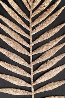 Golden tropical palm leaf on black background close up