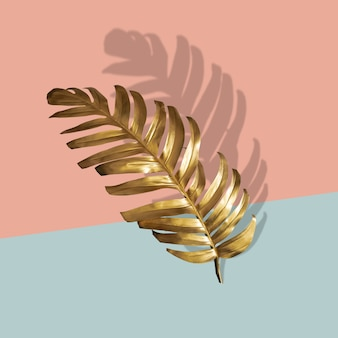 Golden tropical palm leaf monstera on pastel luxury pink  abstract pattern for design and space