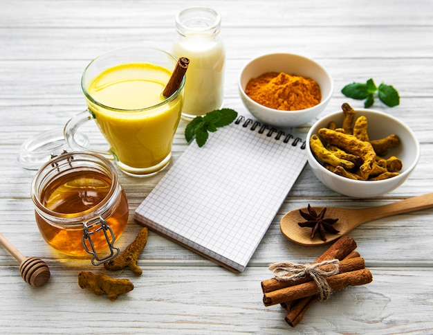 Golden turmeric latte in a glass, spices and recipe book over white wooden background
