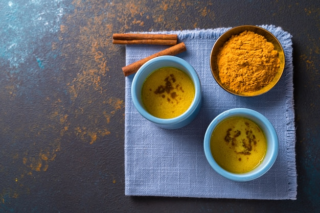 Golden turmeric latte milk made with turmeric and other spices on wooden background.