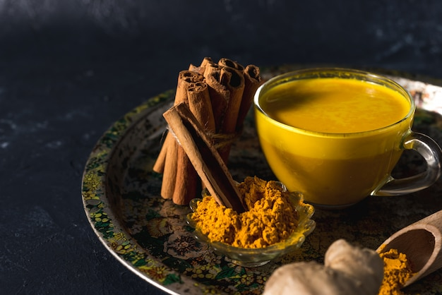 Golden turmeric milk on the dark surface with spices cinnamon and ingredients