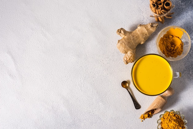 Golden turmeric milk on the white background with spices cinnamon and ingredients