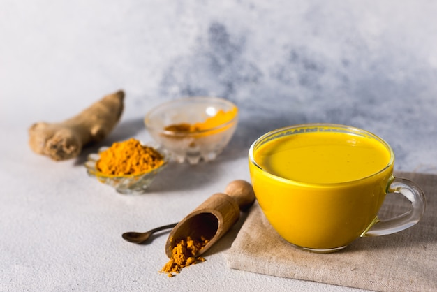 Golden turmeric milk on the white surface with spices cinnamon and ingredients
