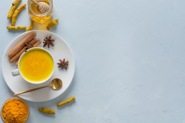 Golden turmeric milk with honey and ingredients on blue.