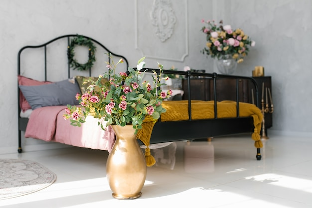Golden vase with flowers near the bed in the bedroom