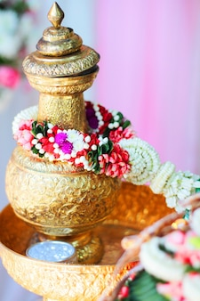 Golden vase with jasmine garland in tradition thai wedding ceremony.
