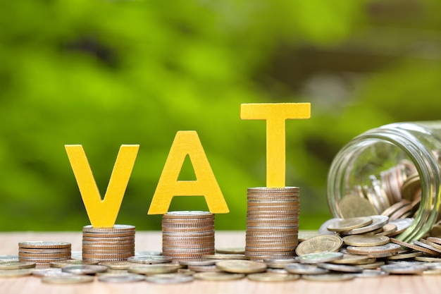 Golden vat word on coins stacked on wooden background.vat concept.