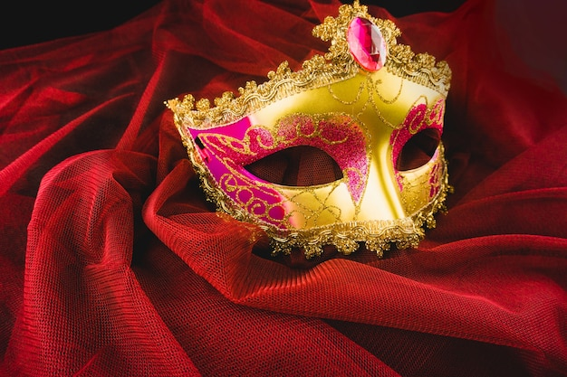 Golden venetian mask on a red fabric