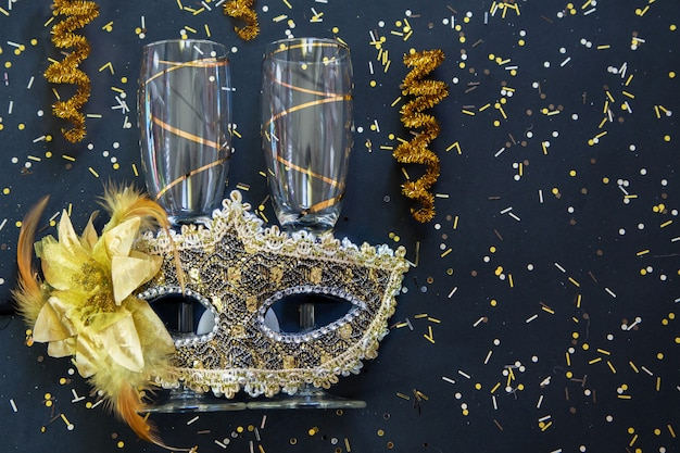 Golden venetian mask with champagne glasses and confetti on black surface