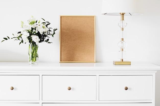 Золотая вертикальная рамка и букет живых цветов на белой мебели роскошного домашнего декора и дизайна ф ...