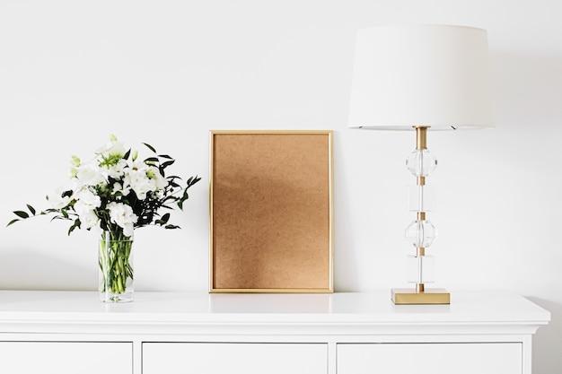 Золотая вертикальная рамка и букет живых цветов на белой мебели роскошный домашний декор и дизайн для создания макетов