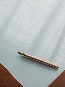 Golden vintage ink pen placed on a piece of white paper
