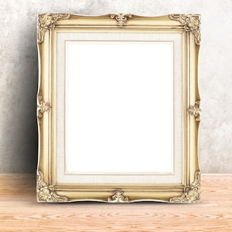 Golden vintage photo frame at concrete wall and wooden table,template mock up for display of product