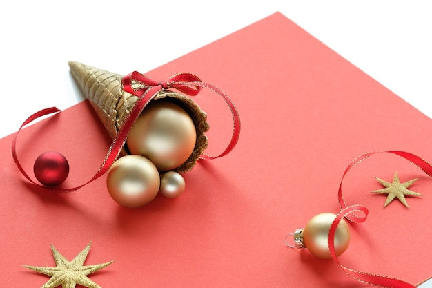 Golden waffle ice cream cone with xmas gold balls, stars and ribbons on coral color paper