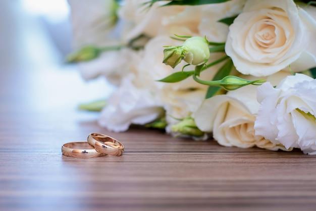Золотые обручальные кольца и свадебный букет из белых роз на столе крупным планом
